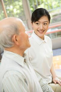 座りながら談笑するシニア男性と介護福祉士の写真素材 [FYI02573028]