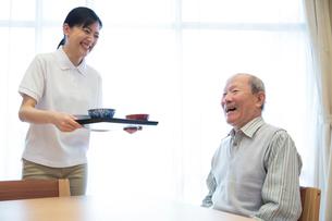 介護施設の朝食を運ぶ介護福祉士とシニア男性の写真素材 [FYI02573033]