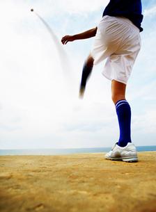 ボールを蹴るサッカーのユニフォーム姿の男性の写真素材 [FYI02583553]