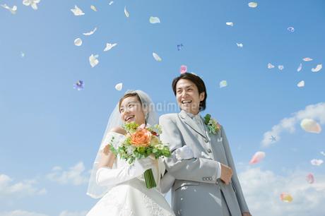 フラワーシャワーをあびる新郎新婦の写真素材 [FYI02583683]