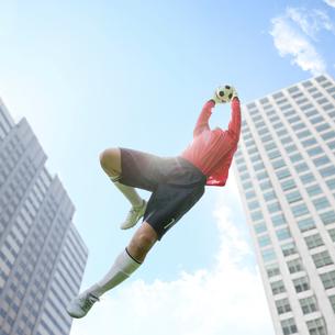 ビルとサッカーボールをつかむゴールキーパーの写真素材 [FYI02584402]