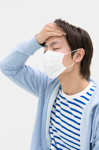 マスクをして額に手をあてる若者男性の写真素材 [FYI02586904]