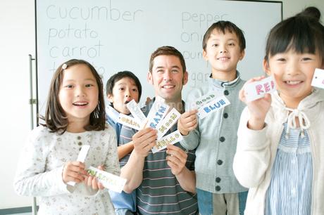 英語の勉強をする小学生と外国人教師の写真素材 [FYI02588953]