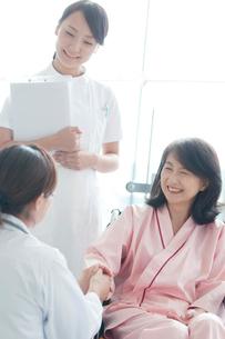 患者の手を握る女医と看護師の写真素材 [FYI02589695]