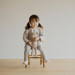 椅子に座りクマのぬいぐるみを持つ女の子の写真素材 [FYI02590172]