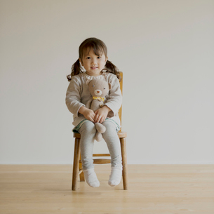 椅子に座りクマのぬいぐるみを持つ女の子の写真素材 [FYI02590509]