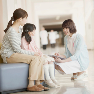 病院の待合室で順番を待つ親子と問診をする看護師の写真素材 [FYI02591349]