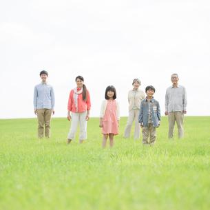 草原で微笑む3世代家族の写真素材 [FYI02591741]
