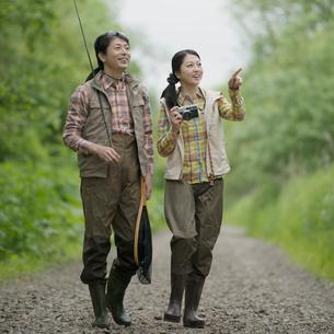釣り道具を持ち山道を歩くミドル夫婦の写真素材 [FYI02591790]