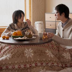こたつでミカンを食べるカップルの写真素材 [FYI02591856]