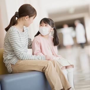 病院の待合室で順番を待つ親子の写真素材 [FYI02591885]