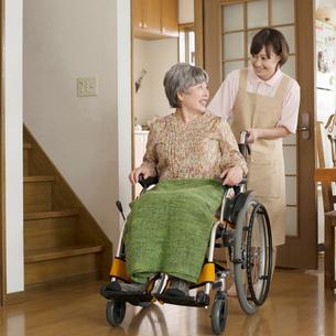 シニア女性の乗る車椅子を押すホームヘルパーの写真素材 [FYI02592407]