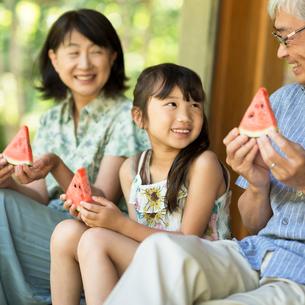 縁側でスイカを食べる祖父母と孫の写真素材 [FYI02593281]