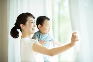 子供を抱きカーテンを開ける母親の写真素材 [FYI02593565]