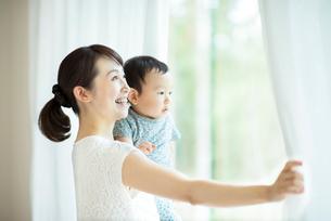 子供を抱きカーテンを開ける母親の写真素材 [FYI02593622]
