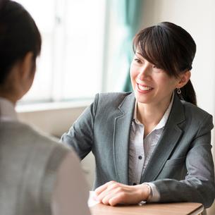 進路相談をする女子学生と女性教師の写真素材 [FYI02593641]