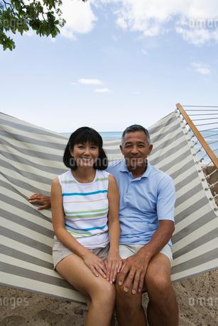 ハンモックに座るシニア夫婦の写真素材 [FYI02594206]