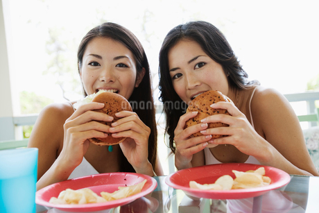 ハンバーガーを食べる日本人女性の写真素材 [FYI02594242]