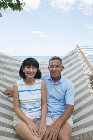 ハンモックに座るシニア夫婦の写真素材 [FYI02594426]