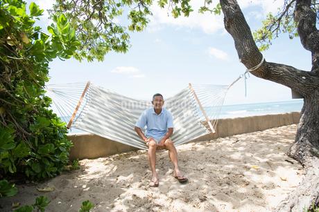 ハンモックに座るシニア男性の写真素材 [FYI02594932]