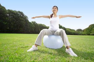 バランスボールを使ってトレーニングする女性の写真素材 [FYI02595583]