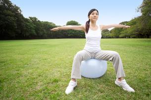 バランスボールを使ってトレーニングする女性の写真素材 [FYI02595712]