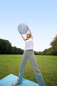 バランスボールを使ってストレッチする女性の写真素材 [FYI02595902]