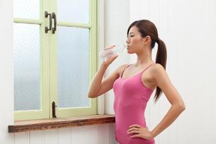 窓辺で水を飲む女性の写真素材 [FYI02596056]