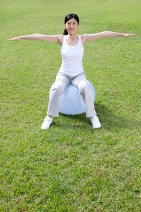 バランスボールを使ってトレーニングする女性の写真素材 [FYI02596162]