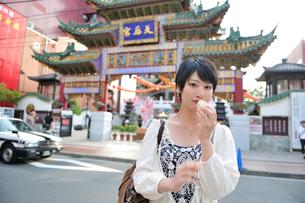 中華街で肉まんを食べてる女性の写真素材 [FYI02596175]