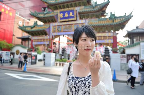 中華街で肉まんを食べてる女性の写真素材 [FYI02596199]