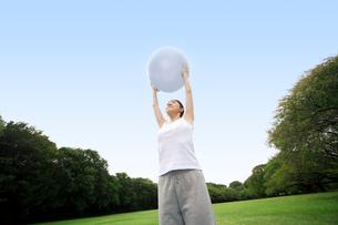 バランスボールを使ってストレッチする女性の写真素材 [FYI02596435]