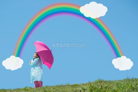 ピンクの傘と長靴でレインコートを着た女の子 虹と雲の写真素材 [FYI02596507]