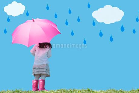 ピンクの傘と長靴の女の子の後ろ姿 雲と雨のしずくの写真素材 [FYI02596587]