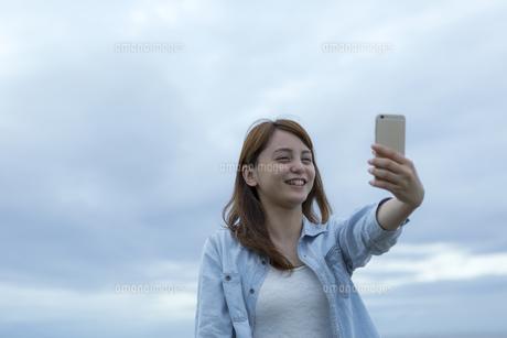 スマートフォンで自分を撮影する女性の写真素材 [FYI02596906]