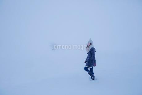雪の中を歩く女性の写真素材 [FYI02596988]