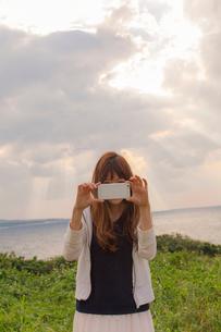 海辺でスマートフォンで撮影する女性の写真素材 [FYI02597248]
