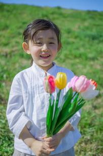 チューリップを持つ笑顔の女の子の写真素材 [FYI02597251]