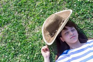 草原で仰向けに寝る女性の写真素材 [FYI02597290]