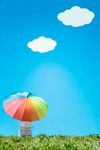 虹色の傘をさす女の子の後ろ姿 青空に雲の写真素材 [FYI02597306]