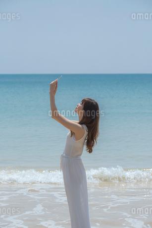 海辺でスマートフォンで撮影する女性の写真素材 [FYI02597312]