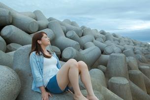 テトラポッドに座って音楽を聴く女性の写真素材 [FYI02597328]