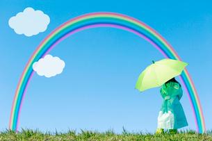 レインコートを着てグリーンの傘をさす女の子の後ろ姿 虹と雲の写真素材 [FYI02597350]