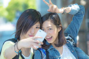 スマートフォンで写真を撮る女性2人の写真素材 [FYI02597381]