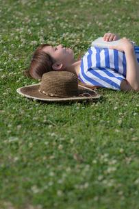 草原で本を持って仰向けに寝る女性の写真素材 [FYI02597396]