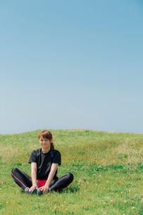 草原でストレッチをする女性の写真素材 [FYI02597418]