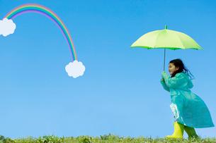 レインコートを着てグリーンの傘をさして歩く女の子 青空と虹の写真素材 [FYI02597441]