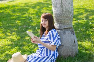 ヤシの木に寄りかかって本を読む女性の写真素材 [FYI02597467]