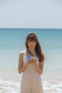 海辺でスマートフォンを操作する女性の写真素材 [FYI02597485]