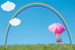 ピンクの傘をさす女の子の後ろ姿 青空に虹と雲の写真素材 [FYI02597507]